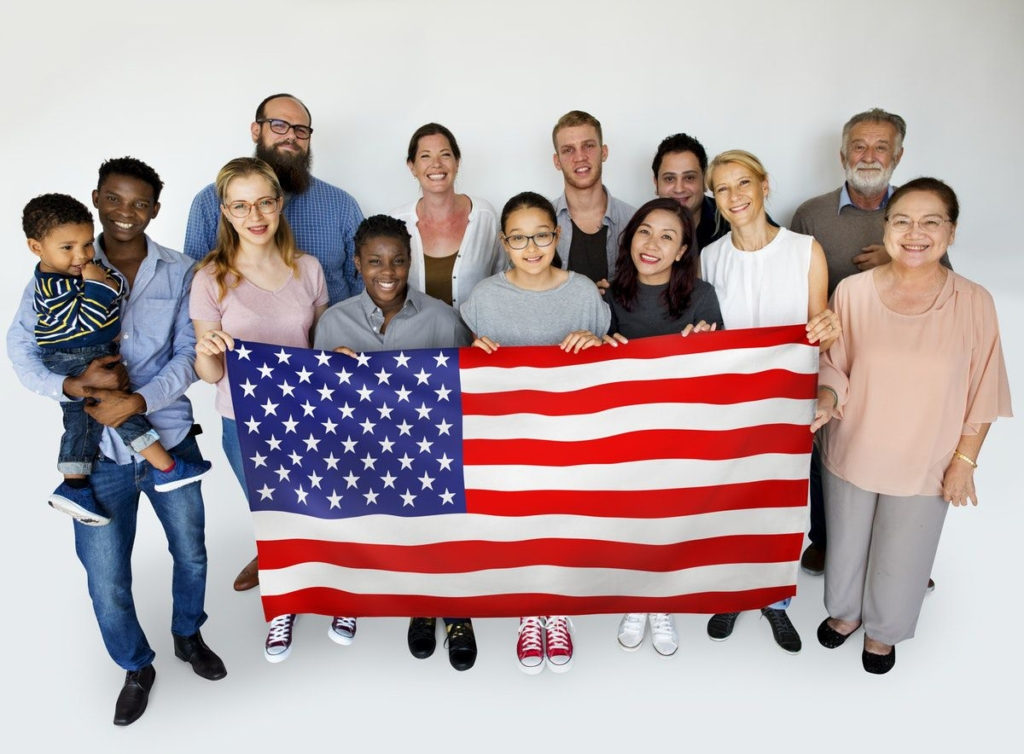 A photo of a diverse group of happy people with the American Flag of United States of America.