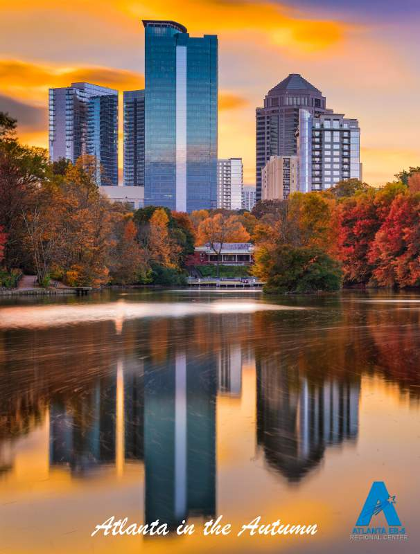 animage of atlanta in the autumn, a part of the cityscape with a refelcting lake in the foreground the clouds are redish as the trees are too it's an image taken at dusk, and there are vibrant yellow, orange and red, it looks very beautiful.